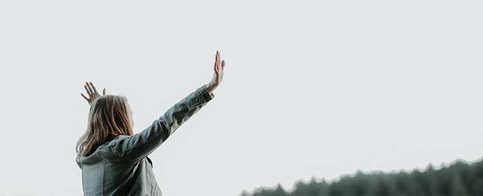 woman raising hands and praising God